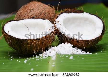 Fresh coconut cut open in half isolated on green banana leaf background Kerala India. Grated coconut top view. for cooking, frying, seasoning sambar, chutney.desiccated coconut oil    - stock photo