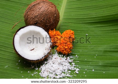 Fresh coconut cut open in half isolated on green banana leaf background Kerala India. Grated coconut top view. for cooking, frying, seasoning sambar, chutney. desiccated coconut oil  spa - stock photo
