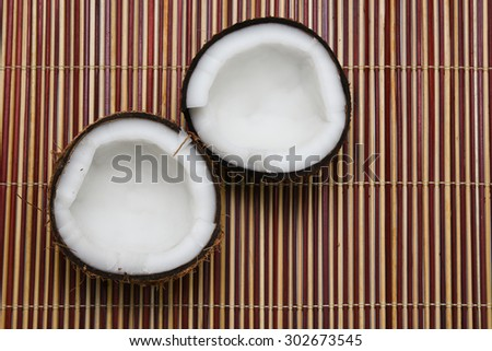 Fresh coconut cut open in half on bamboo mat background Kerala India - stock photo