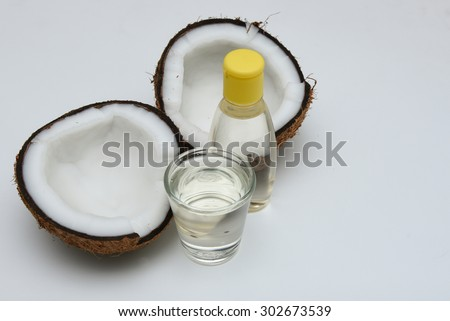 Fresh coconut cut open in half with extra clear and pure cooking/massage coconut oil in a glass and bottle for alternative therapy spa. isolated on white background. - stock photo