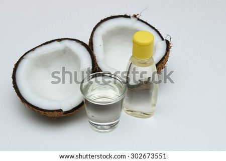 Fresh coconut cut open in half with extra clear and pure cooking/massage coconut oil in a glass and bottle for alternative therapy spa. Isolated on white background - stock photo