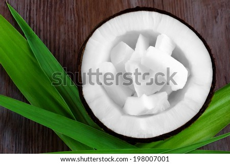 Fresh coconut - opened with coconut chips on green leaves on wooden background - close up - stock photo
