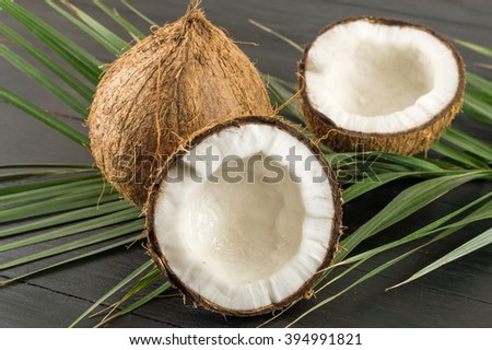Fresh coconuts and coconut leaves on dark wooden table - stock photo