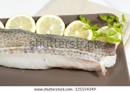 Fresh cod fillet with fresh lemon slices - stock photo