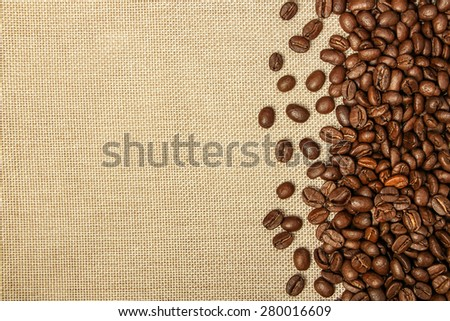 Fresh coffee bean is on the burlap sack background. - stock photo