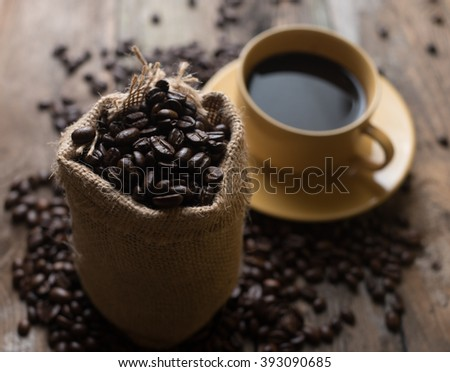 Fresh coffee beans on wood and linen bag, ready to brew delicious , burlap sack and yellow cup