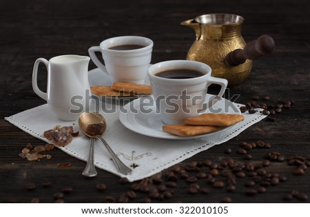 Fresh coffee cups, Turk. Ground coffee, crackers and coffee beans in a wooden bowl on the vintage wooden background.