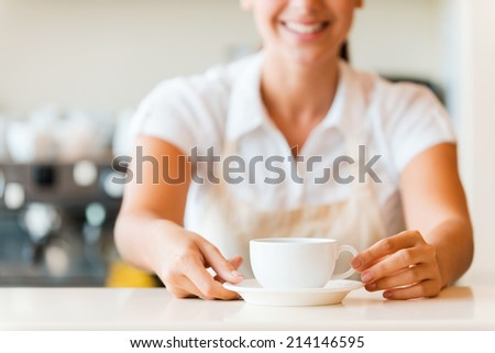 Fresh coffee for you. Close-up of beautiful young woman in apron serving coffee and smiling while standing in coffee shop - stock photo