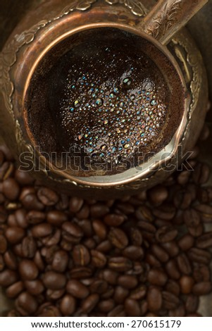 Fresh coffee in coffee pot with beans  (top view, close-up) - stock photo