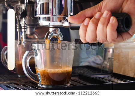 Fresh coffee in the coffee machine - stock photo