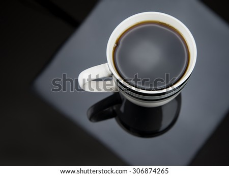 Fresh Coffee pouring into fancy cup on table top