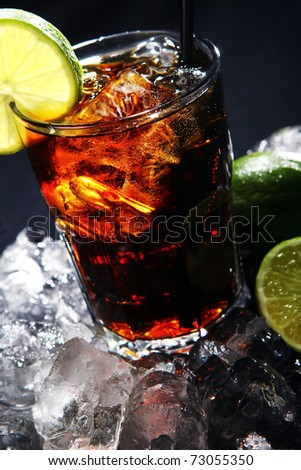 Fresh cola drink with ice and green lime on black background - stock photo