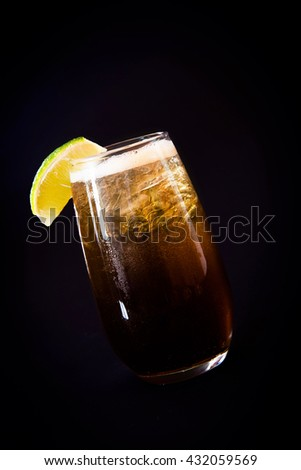 Fresh cola drink with ice and lime on black background