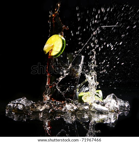 Fresh cola drink with splashesh of water and green lime on black background - stock photo