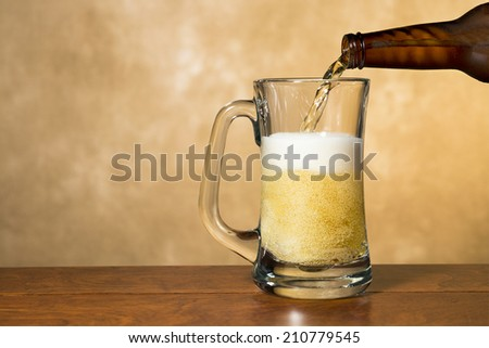 Fresh, cold, crisp beer being poured into a classic pint mug against a mottled golden background. - stock photo