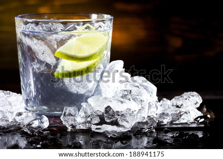 fresh cold drink with lime slice and ice in transparent glass on wooden table