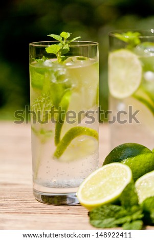 fresh cold refreshment drink mineral water soda with lime and mint on wooden table in summer