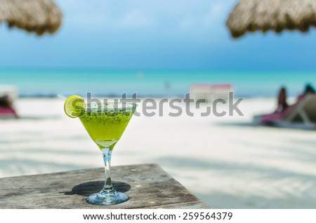 Fresh cold tasty Margarita cocktail with lime and ice on a table at tropical white sand beach - stock photo