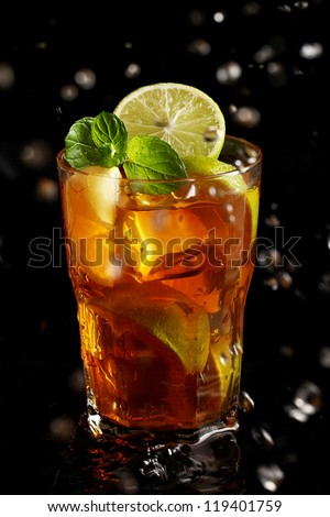 Fresh cold tea with lemon, lime and mint in water splashing - stock photo