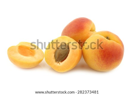 fresh colorful apricots and a cut one on a white background - stock photo