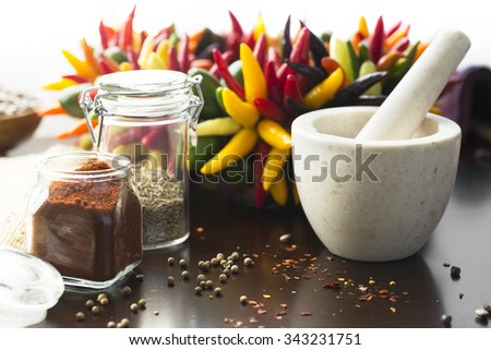 Fresh colorful chili peppers and ground chili pepper with mortar and pestle. - stock photo