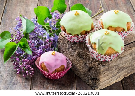 Fresh colorful cupcakes with frosting and sugar beads on a thick wooden board, branch of lilac. Rustic style. Selective focus - stock photo