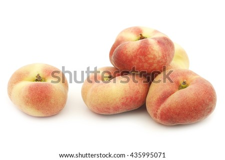 fresh colorful flat peaches (donut peaches) on a white background - stock photo