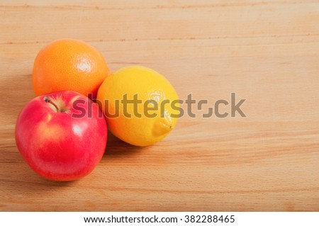 Fresh colorful fruits - apple, lemon and orange on wooden background. Delicious source of vitamins after winter.
