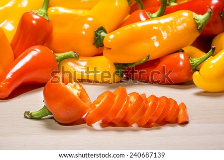 Fresh, colorful mini bell peppers on a chopping board being chopped for use as a cooking ingredient - stock photo