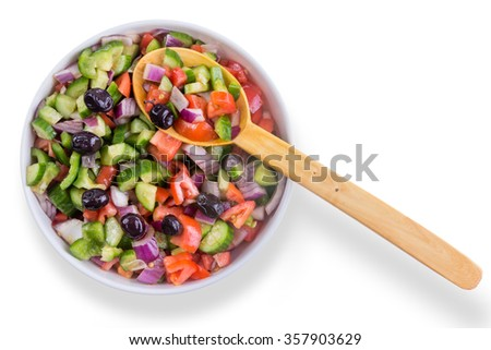 Fresh colorful Turkish shepherd salad with olives served in a round bowl with a wooden serving spoon as a healthy accompaniment to a meal, overhead on white