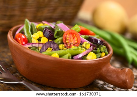 Fresh colorful vegetarian salad made of green beans, cherry tomatoes, sweet corn, black olives and red onions in rustic bowl (Selective Focus, Focus on the tomato in the middle)  - stock photo
