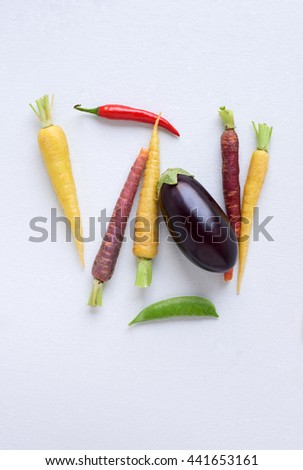 Fresh colourful local organic vegetables on white background, eggplant, heirloom carrots, chilli and snap pea - stock photo