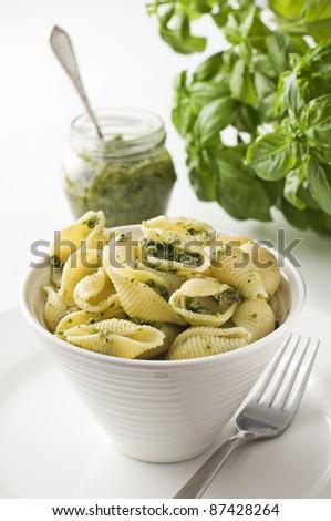 Fresh conchiglioni pasta with basil pesto sauce - stock photo