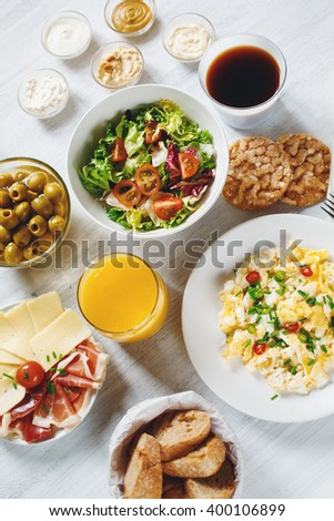 Fresh Continental Breakfast. Healthy Different Food. Scrambled Eggs, Salad, Cheese, Prosciutto, Coffee and Juice. Concept of Business or Vacation Breakfast. View from Above.  - stock photo
