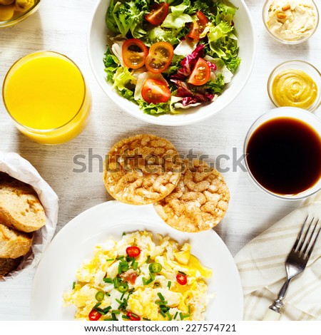 Fresh continental breakfast. Healthy food. Scrambled eggs, salad, cheese, prosciutto, coffee and juice. Concept of business or holiday breakfast. Top view. Instagram effect. - stock photo