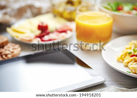 Fresh continental breakfast. Tablet, black screen, selective focus. Concept of business or holiday breakfast. Background, shallow depth of field. - stock photo