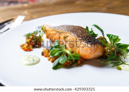 Fresh cooked fish with vegetables and salad