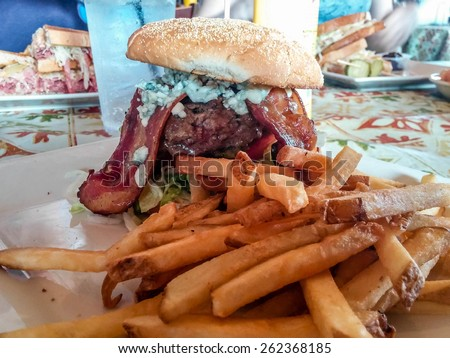 Fresh cooked french fries with a massive bacon, blue cheese burger at a restaurant - stock photo
