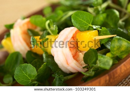 Fresh cooked shrimp, mango and avocado on skewer with watercress leaves on wooden plate (Selective Focus, Focus on the front rim of the shrimp) - stock photo