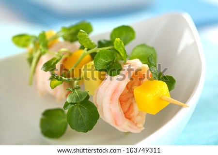 Fresh cooked shrimp, mango and avocado on skewer with watercress leaves over bowl (Selective Focus, Focus on the upper rim of the shrimp) - stock photo