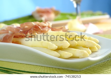 Fresh cooked white asparagus served with ham with white wine and green asparagus in the background (Selective Focus, Focus on the front of the asparagus on the left) - stock photo