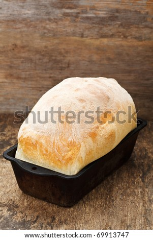 Fresh cooked white bread still in the bread pan - stock photo
