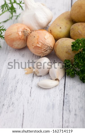 Fresh cooking ingredients with garlic cloves, onions and potatoes together with fresh herbs on a white rustic wooden surface with copyspace