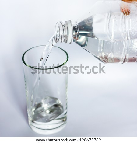 Fresh cool water pouring from a clean plastic water bottle. - stock photo