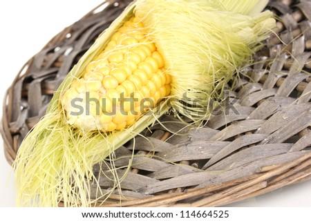 Fresh corn cob on wicker mat isolated on white - stock photo