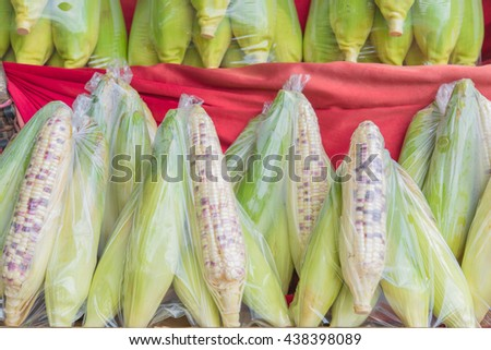 Fresh corn in pack for sell on red fabric - stock photo