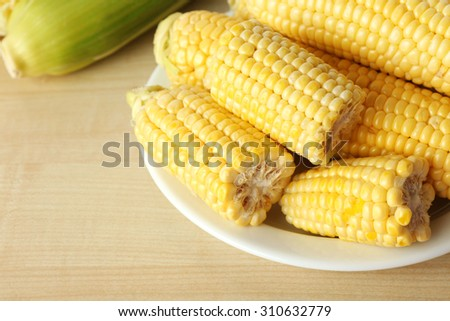 Fresh corn on cobs in plate on wooden table, closeup - stock photo