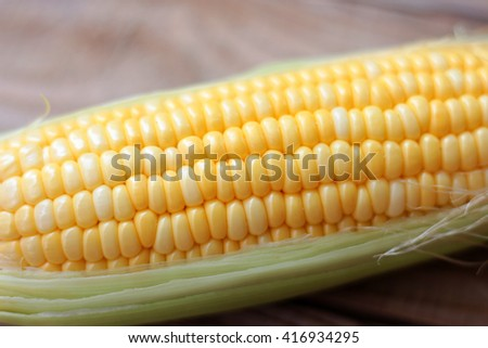 Fresh corn on cobs on rustic wooden table, closeup soft focus