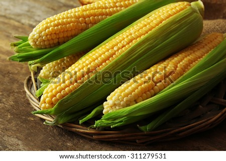 Fresh corn on cobs on wicker mat on wooden table, closeup - stock photo