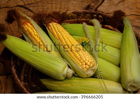 Fresh corn on cobs on wicker mat on wooden table, closeup - stock photo